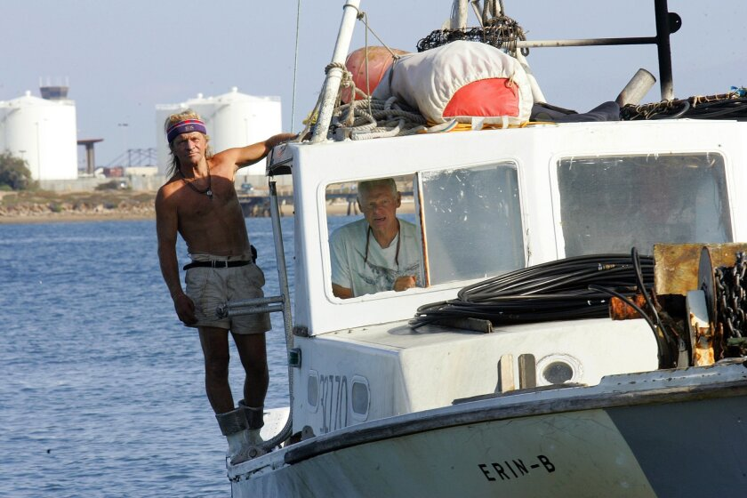 Kenny Jeavons (left) and Peter Halmay arrived back in San Diego Bay after a day of harvesting sea urchins. (Nelvin C. Cepeda / Union-Tribune)