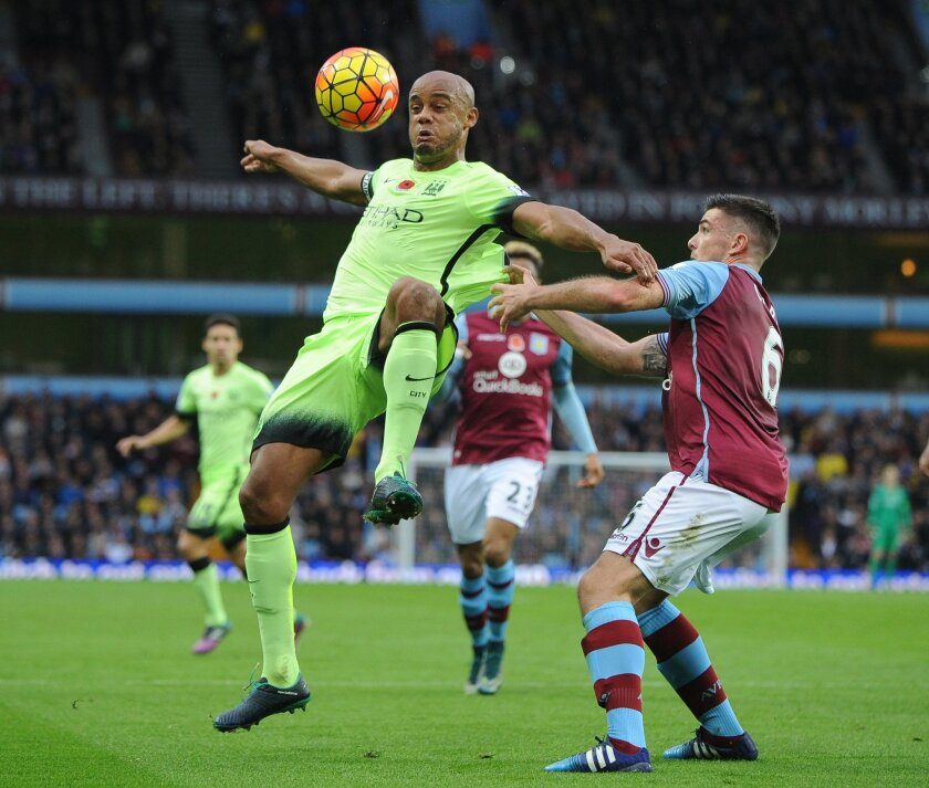 Manchester City's Vincent Kompany, left, controls the ball from Aston Villa's Ciaran Clark during the English Premier League soccer match between Aston Villa and Manchester City at the Villa Park, Birmingham, England, Sunday, Nov. 8, 2015. (AP Photo/Rui Vieira)