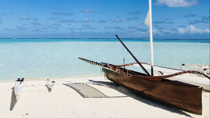 A Tahitian outrigger canoe sits on the powdery shores of Teti'aroa
