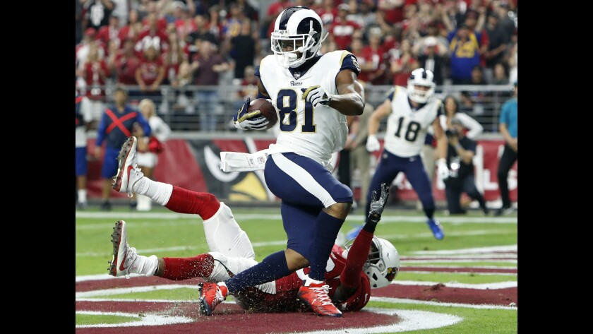 Rams tight end Gerald Everett scores a touchdown as Arizona Cardinals safety Budda Baker defends during the first half.
