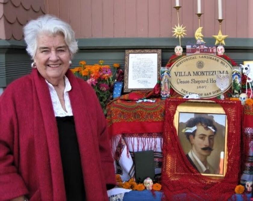 Kay Porter stands by a Dia de los Muertos altar in front of the Villa Montezuma Museum