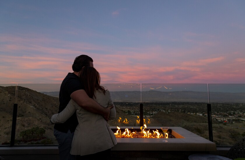 A couple enjoys the view and the warmth of an outdoor fire pit at the Ritz-Carlton in Rancho Mirage.