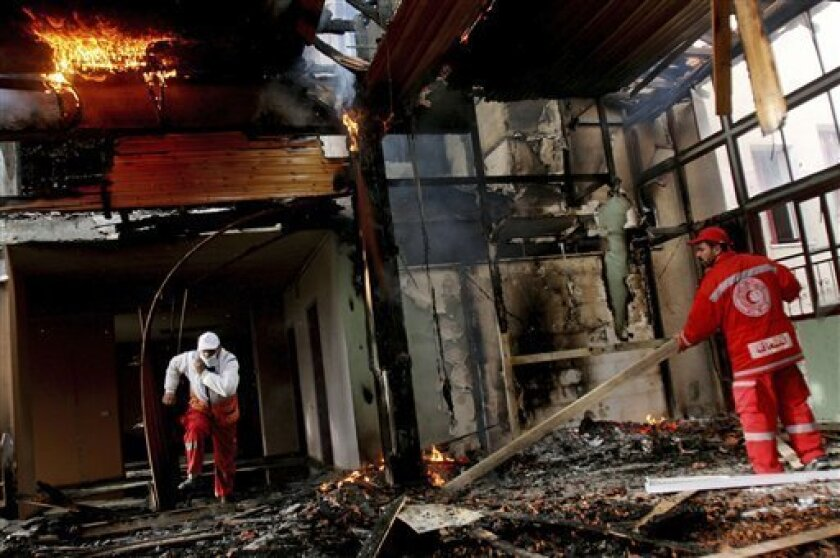 Palestinian medics examine the damage inside a burning building of the Quds hospital after is was hit during Israeli military operations in Gaza City, Friday, Jan. 16, 2009. On Thursday an artillery shell hit the Quds Hospital pharmacy, and another shell landed on its front steps early in the day.