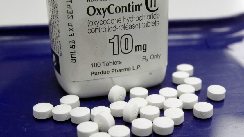 FILE - This Feb. 19, 2013, file photo, shows OxyContin pills arranged for a photo at a pharmacy in M