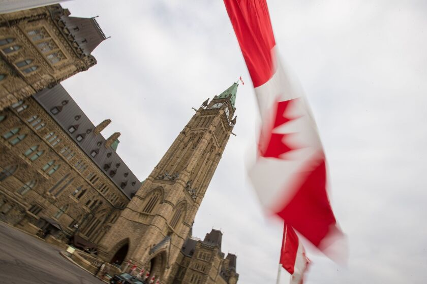 A Canadian flag waves in front of the peace tower on Parliament Hill in Ottawa.