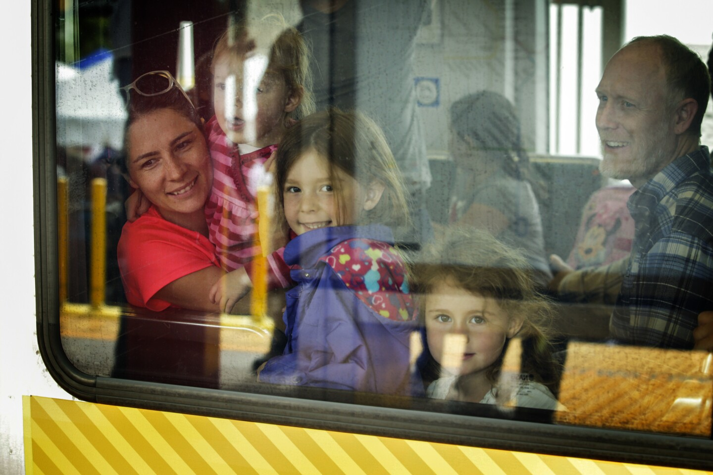 A family enjoys a ride on the Metro Gold Line train on the opening day of service on the $1-billion, 11.5-mile extension through the Foothills. The line will transform the lives and commutes of San Gabriel Valley residents, officials say.