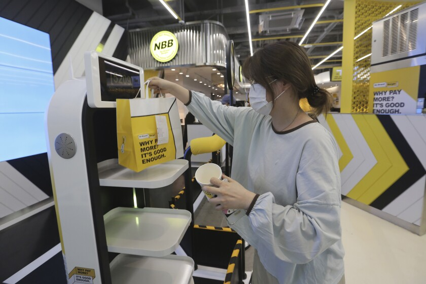 In this Sunday, Sept. 13, 2020, photo, a customer picks up a takeaway bag with food from a robot at No Brand Burger in Seoul, South Korea. These robotic services, with not a single face-to-face interaction, have been seen as a selling point amid the coronavirus pandemic and its restrictions. (AP Photo/Ahn Young-joon)