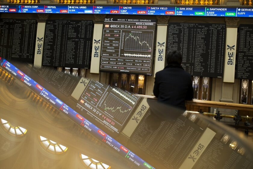 A man looks at screens displaying financial information at the Stock Exchange in Madrid, Spain, Tuesday, Feb. 9, 2016. Renewed jitters about the global economy set off a wave of selling in banking stocks after Asian markets tumbled Tuesday, led by a 5.4 percent slide in Tokyo. The stock index in Sp