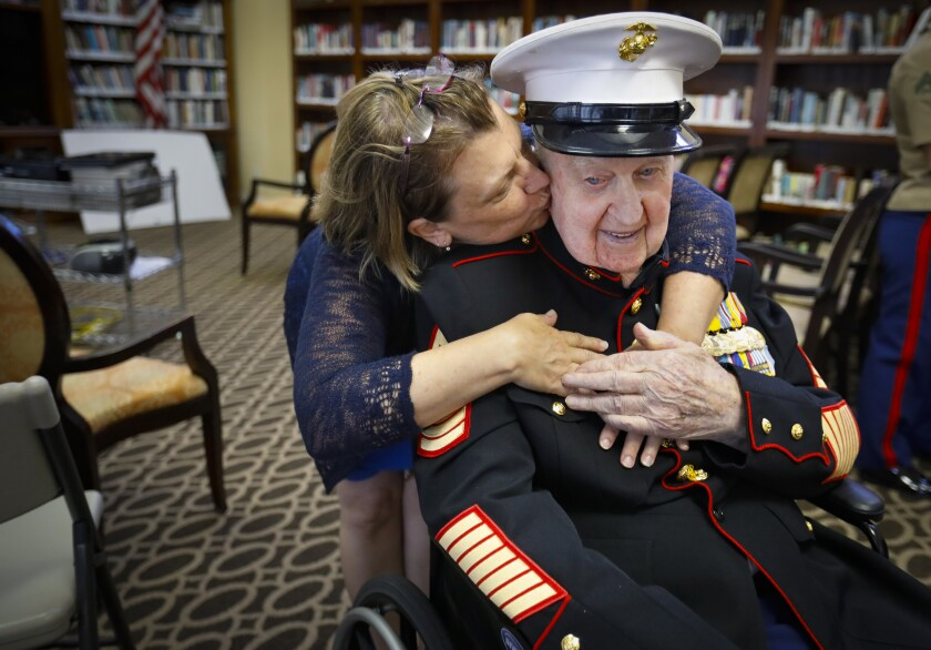 Retired U.S. Marine Corps First Sergeant John Farritor, wearing his dress uniform, is a veteran of some of the biggest battles of World War II in the Pacific and the Korean War, gets a hug and a kiss from his friend Kathryn Turner, during a party celebrating his 100th birthday, at Pacifica Senior Living, July 9, 2019, in Vista, California, where he lives.