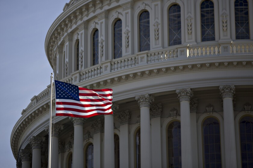 The American flag flies next to the dome of the Capitol on Jan. 15, 2017. The House voted Feb. 6, 2018, to prohibit sexual relationships between lawmakers and their employees.