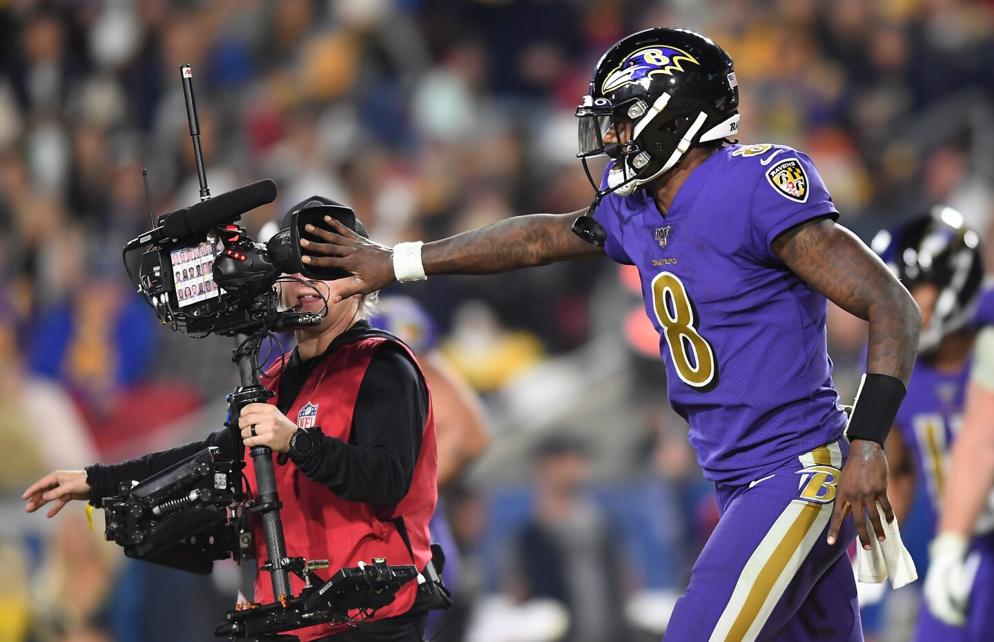 LOS ANGELES, CALIFORNIA NOVEMBER 25, 2019-Ravens quarterback Lamar Jackson covers the lens form a televison cameraman after his team scored a touchdown against the Rams in the 4th quarter at the Coliseum Sunday. (Wally Skalij/Los Angerles Times)