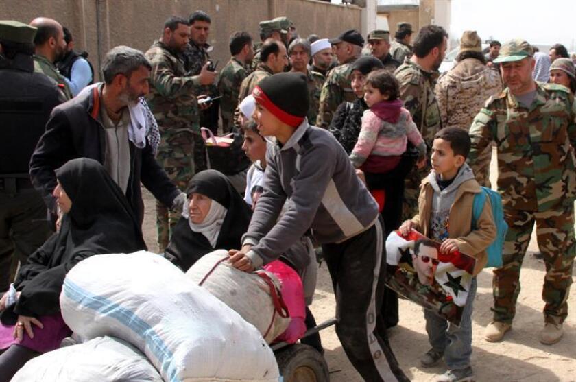 Un niño lleva un retrato del presidente sirio, Bachar al Asad, mientras abandona, junto a cientos de civiles, la zona de Guta Oriental, en la zona rural de Damasco (Siria). EFE