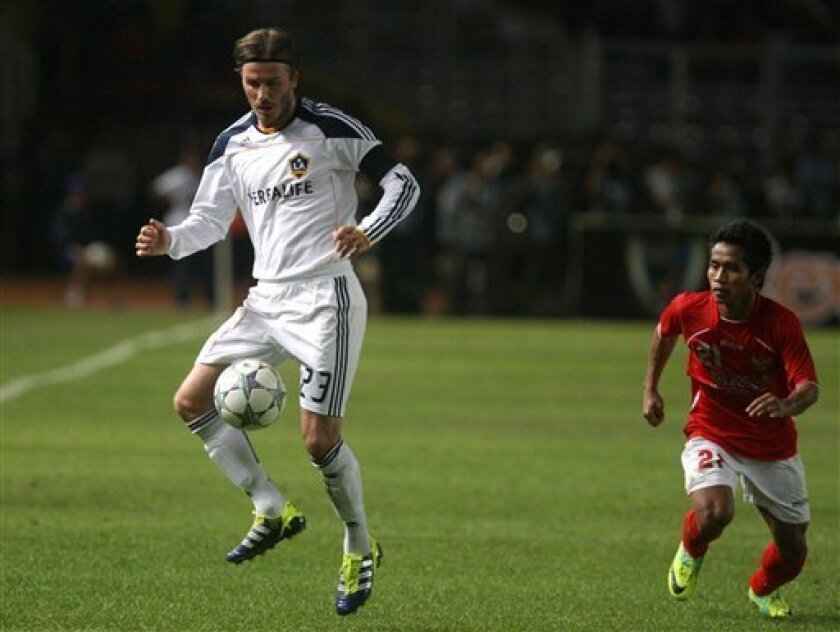 Los Angeles Galaxy's David Beckham, left, fights for the ball with Indonesia Selection's Andik Vermansyah, right, during their friendly match at Gelora Bung Karno stadium in Jakarta, Indonesia, Wednesday, Nov. 30, 2011. The match was part of LA Galaxy's Asia Pacific Tour. (AP Photo/Dita Alangkara)
