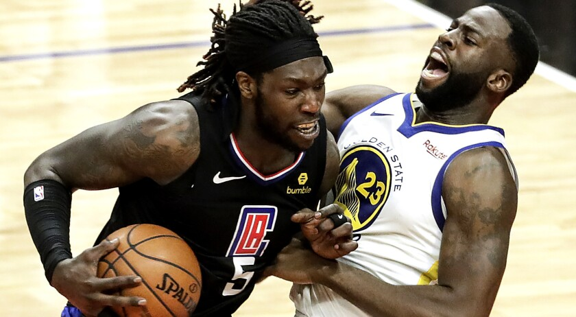 Clippers center Montrezl Harrell tries to power his way past Warriors forward Draymond Green during a game last season.