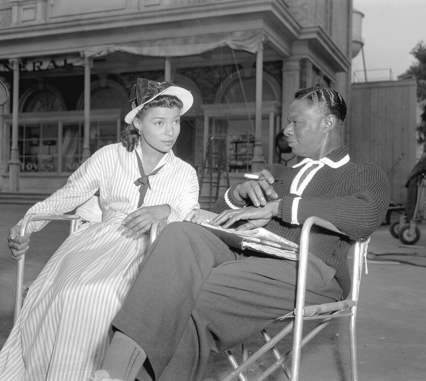"""Ruby Dee (1922-2014) -- The film, stage and TV actress with Nat King Cole relaxing on the set of """"St. Louis Blues"""" in 1957."""