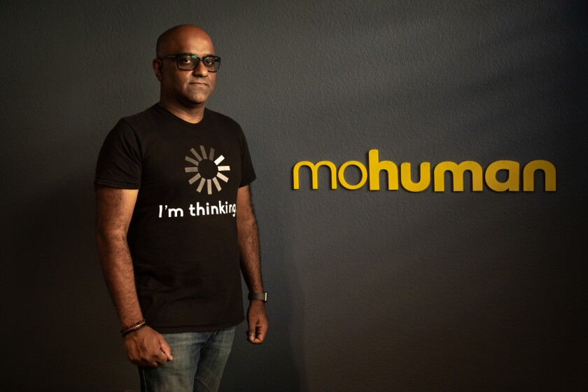 Nishal Mohan, standing against a dark grey wall with the name of his nonprofit, mohuman, in yellow on the wall