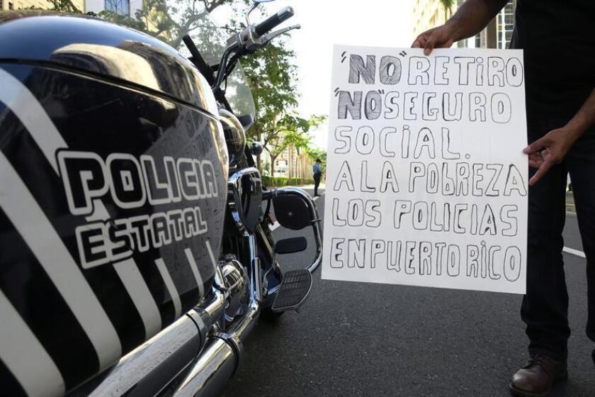 Un manifestante muestra un cartel el lunes 22 de enero de 2018, durante una protesta de la Policía de Puerto Rico frente a las oficinas de la Junta de Supervisión Fiscal (JSF) en San Juan (Puerto Rico) para reclamar una jubilación digna y el pago de horas extras. EFE/Archivo