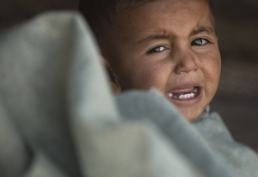 A Syrian Kurdish refugee baby from the Kobani area cries in a tent at a camp in Suruc, on the Turkey-Syria border Wednesday, Nov. 19, 2014. Kobani, also known as Ayn Arab, and its surrounding areas, has been under assault by extremists of the Islamic State group since mid-September and is being def