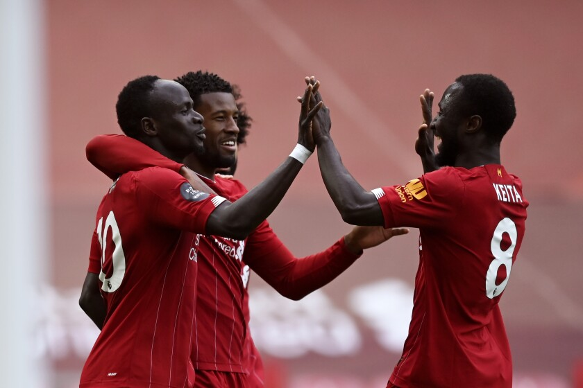 Liverpool's Sadio Mane, left, celebrates after scoring the opening goal during the English Premier League soccer match between Liverpool and Aston Villa at Anfield Stadium in Liverpool, England, Sunday, July 5, 2020. (Shaun Botterill/Pool via AP)
