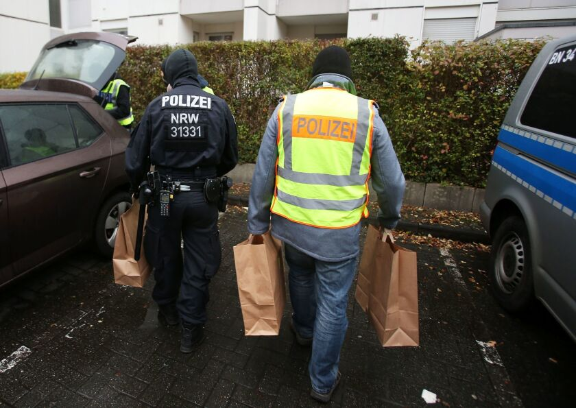 Police officers carry confiscated material to a car after raiding an apartment building in Bonn on Nov. 15.