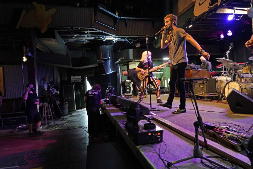 """FILE - In this Oct. 26, 2020 file photo, David Shaw, foreground, frontman for the band The Revivalists, performs with actor Harry Shearer, co-author and character in the movie """"This Is Spinal Tap,"""" as they record a video stream concert with the band Galactic, inside an empty Tipitina's music club, in New Orleans. Entertainment venues in New Orleans have been given permission to start hosting live music again starting this weekend, but under strict regulations. Mayor LaToya Cantrell and city health director Jennifer Avegno announced the change Wednesday, March 10, 2021. (AP Photo/Gerald Herbert, File)"""
