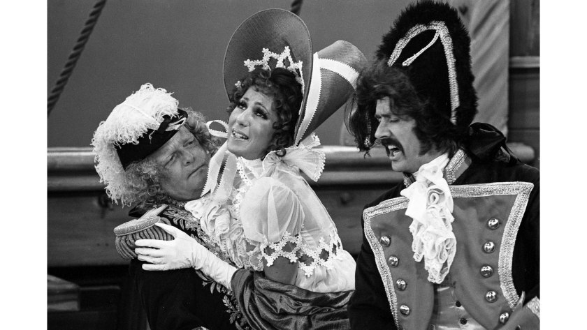 Three actors in costume perform a comedy sketch