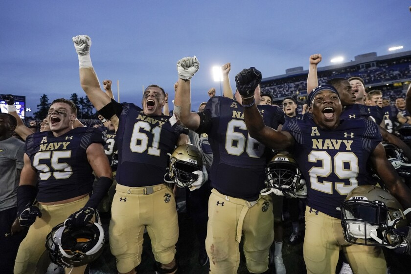 Navy players celebrate after defeating UCF 34-30 during an NCAA college football game, Saturday, Oct. 2, 2021, in Annapolis, Md. (AP Photo/Julio Cortez)