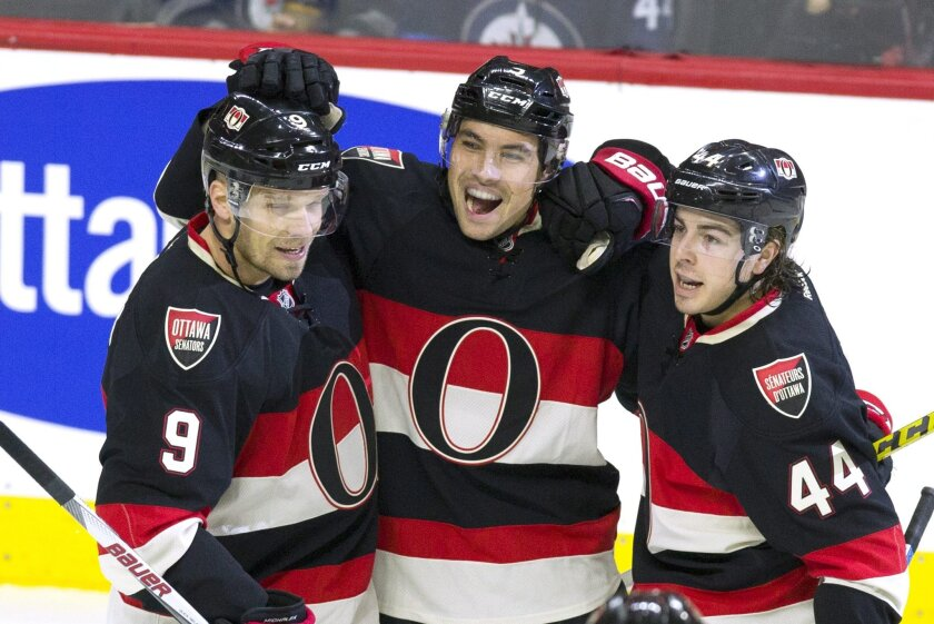 Ottawa Senators' Cody Ceci, center, celebrates his goal with teammates Jean-Gabriel Pageau (44) and Milan Michalek (9) during the first period of an NHL hockey game against the Winnipeg Jets on Thursday, Nov. 5, 2015, in Ottawa, Ontario. (The Canadian Press via AP)