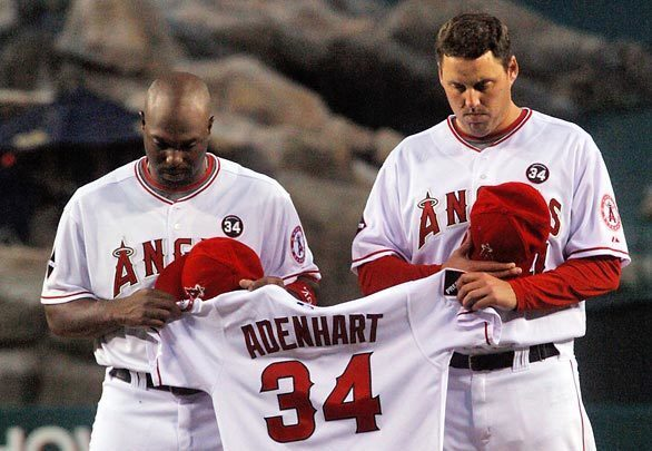 Angels Torii Hunter and John Lackey hold the jersey of pitcher Nick Adenhart, who died of injuries suffered in a car accident Thursday.