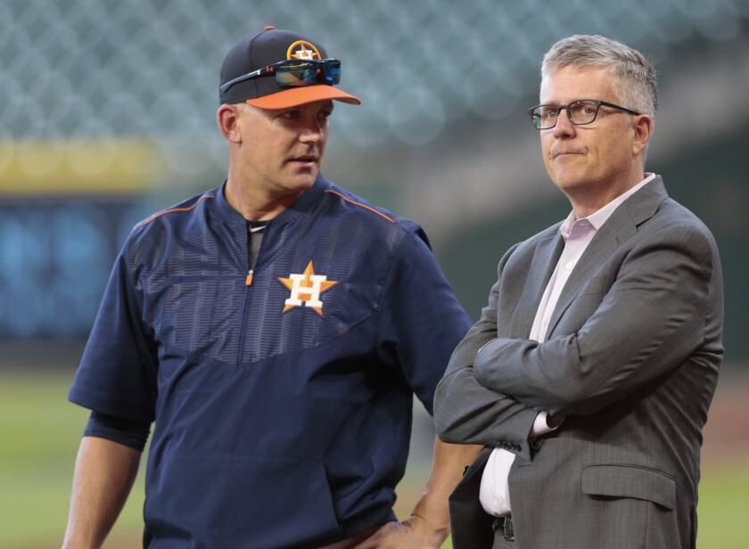 A.J. Hinch, left, and Jeff Luhnow talk during batting practice April 4, 2017, in Houston.