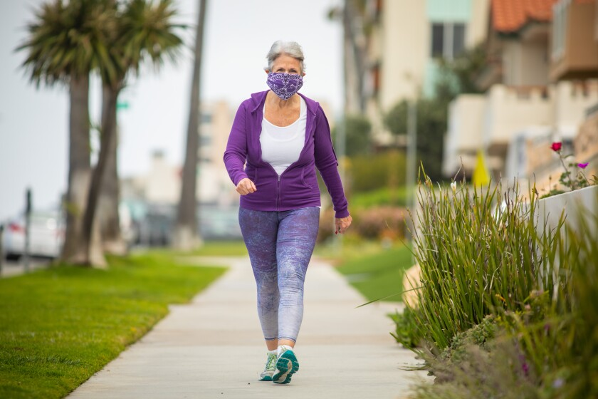 Joan Irvine wears a mask fashioned from a bandanna and hair ties while walking along the Esplanade in Redondo Beach on Thursday.