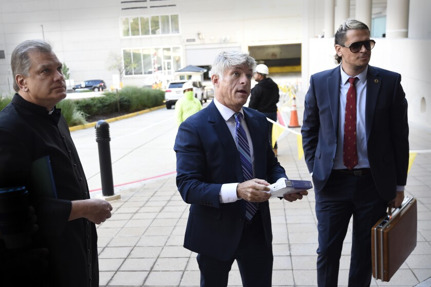 FILE - Fr. Paul Kalchik, left, St. Michael's Media founder and CEO Michael Voris, center, and Milo Yiannopoulos talk with a court officer before entering the federal courthouse, Sept. 30, 2021 in Baltimore. A federal judge has blocked Baltimore city officials from banning the conservative Roman Catholic media outlet from holding a prayer rally at a city-owned pavilion during a U.S. bishops' meeting next month. U.S. District Judge Ellen Hollander ruled late Tuesday, Oct. 13, 2021 that St. Michael's Media is likely to succeed on its claims that the city discriminated against it on the basis of its political views and violated its First Amendment free speech rights. (AP Photo/Gail Burton, file)