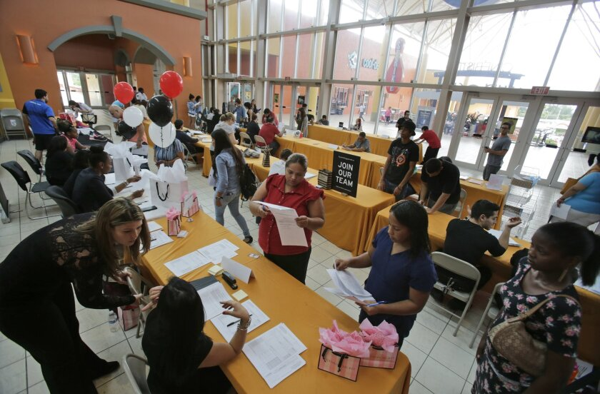FILE - In this Tuesday, Oct. 6, 2015, file photo, people attend a job fair at Dolphin Mall in Miami. The federal government issues its October jobs report Friday, Nov. 6, 2015. (AP Photo/Wilfredo Lee, File)