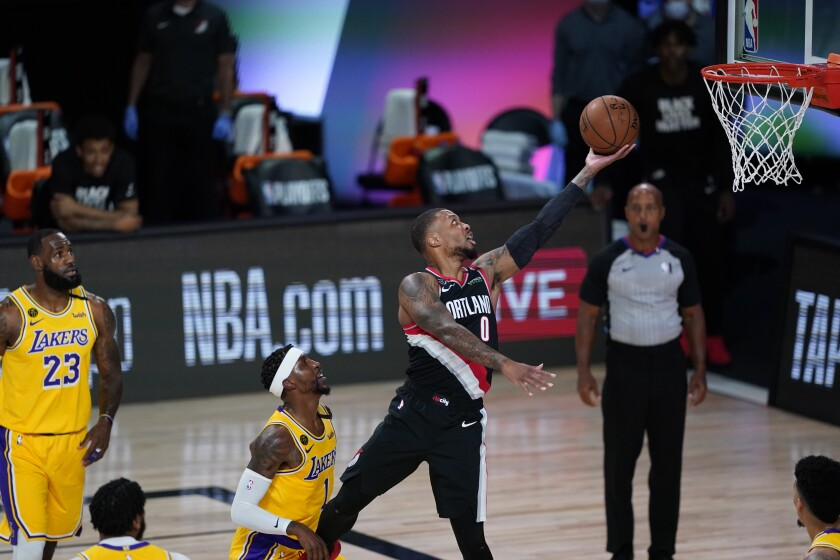 Portland Trail Blazers' Damian Lillard goes to the basket over Lakers' Kentavious Caldwell-Pope.