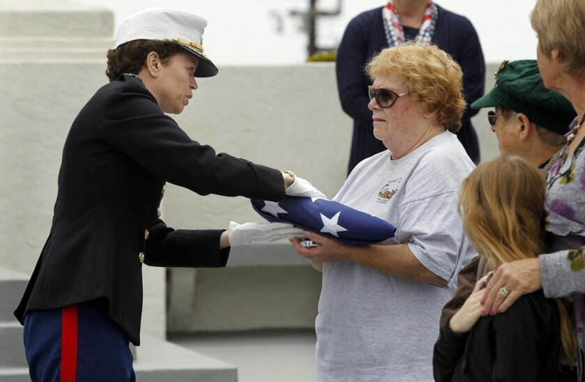 Colonel Stephanie Smith (left) presents a U.S. flag to Joie Chandler (right) daughter of Shirley Kornegay on Thursday during her memorial ceremony at Fort Rosecrans National Cemetery in San Diego, California. Korneygay was one of the first 1000 women to join the United States Marines Corps during WWII.