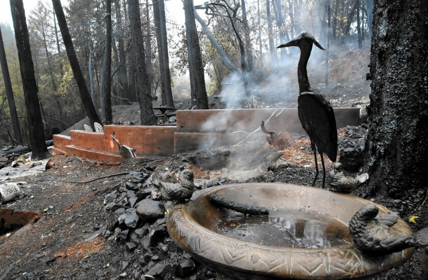 Smoke rises from the charred remains of a home and garden in Anderson Springs.