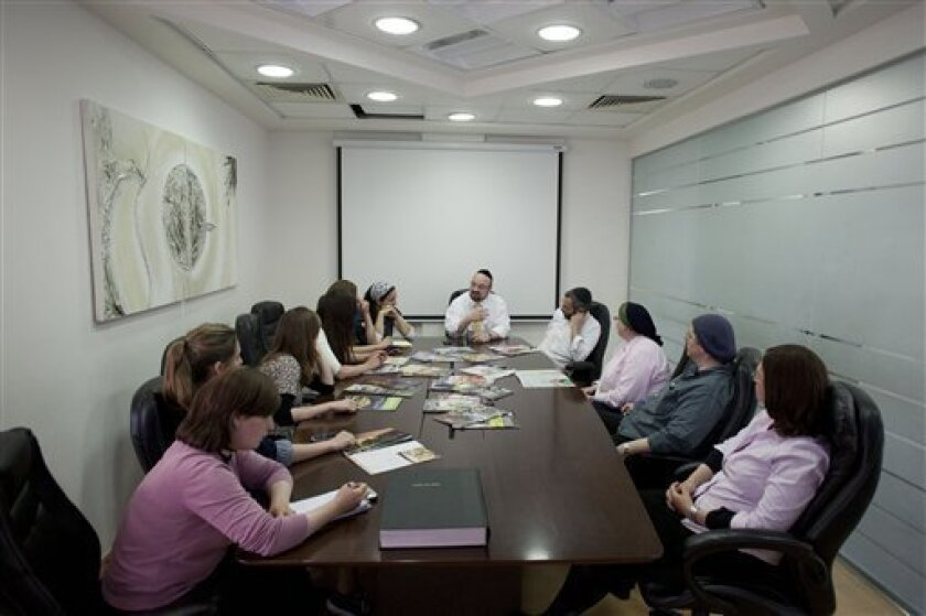 """In this photo taken Monday June 27, 2011, staff of the English edition of the weekly newspaper """"Mishpacha"""" gather during a meeting at the Mishpacha office in Jerusalem. The community of ultra-Orthodox Jews in Israel, long an insular island where rabbis ruled and the outside world was viewed with suspicion or ignored altogether, is being quietly and profoundly altered by a proliferation of new media outlets shining a light on topics that were long taboo. (AP Photo/Bernat Armangue)"""