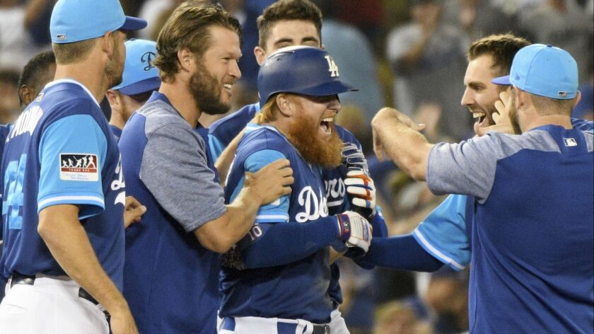 Teammates mob Los Angeles Dodgers' Justin Turner, center, after he hit an RBI-double in the 12th inning of a baseball game to beat the San Diego Padres 5-4, Saturday, Aug. 25, 2018, in Los Angeles.