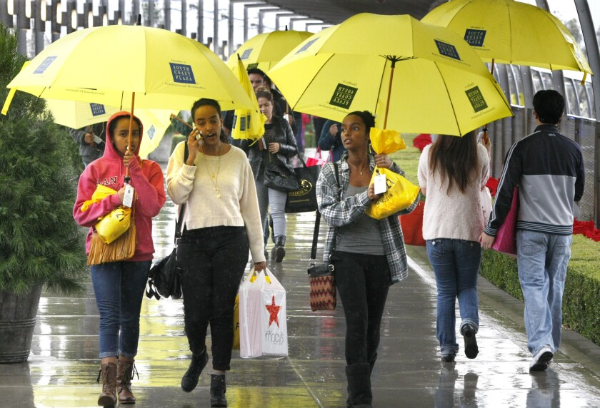 Shoppers armed with borrowed umbrellas and bags of sale items walk through South Coast Plaza on a rainy Black Friday morning, Nov 29, 2013.