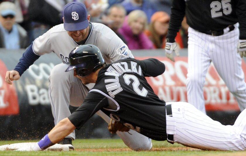 San Diego Padres third baseman Chase Headley tags out Colorado Rockies' Troy Tulowitzki (2) at third base during the third inning of an MLB baseball game, Saturday, May 14, 2011, in Denver.