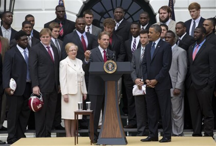 President Barack Obama listens as University of Alabama Crimson Tide head coach Nick Saban, center, speaks during a ceremony honoring the BCS National Champion University of Alabama Crimson Tide football team, Monday, April 15, 2013, on the South Lawn of the White House in Washington. University of