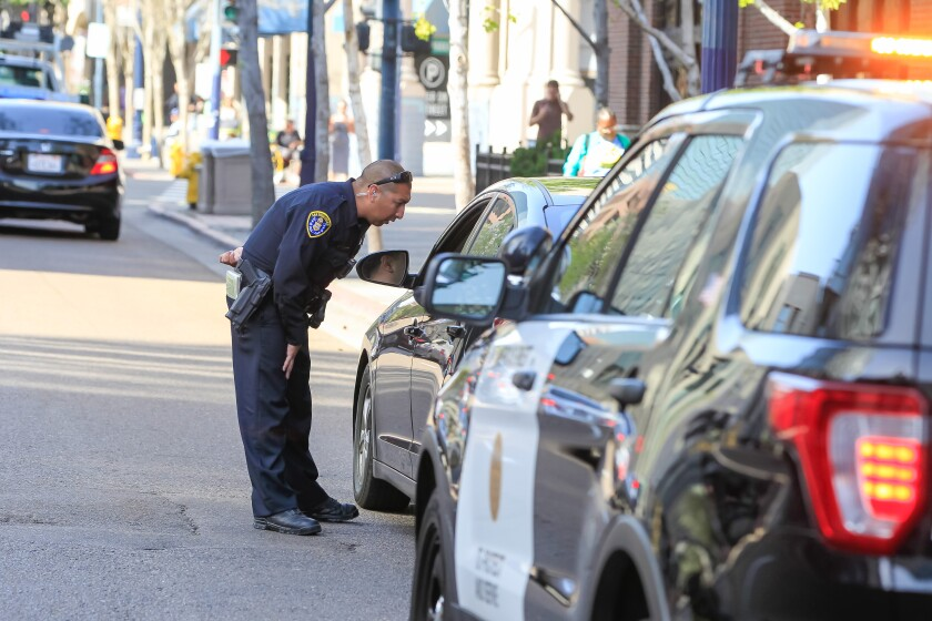 A San Diego police officer talks with a motorist after pulling him over downtown.