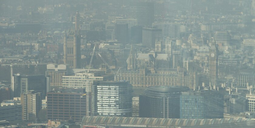 A general view of London from the viewing platform of the Shard building, which has been photographed through plate glass, showing Britain's parliament, the Palace of Westminster and Big Ben's clock tower, right, visible through the haze and smog in London, Friday, April 10, 2015. Southern Britain and northern France are suffering high levels of air pollution due to stagnant air, though an Atlantic weather system will bring fresher conditions Saturday. (AP Photo/Alastair Grant)