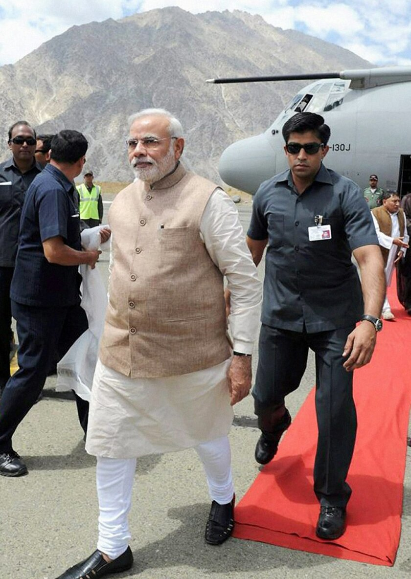 Indian Prime Minister Narendra Modi walks upon his arrival in Kargil, India, Tuesday, Aug. 12, 2014. Modi on Tuesday accused Pakistan of waging a proxy, terrorist war because it was too weak to fight a conventional one, a day after India accused its traditional rival of violating cease-fire agreements in the disputed Himalayan region of Kashmir. (AP Photo/Press Trust of India)
