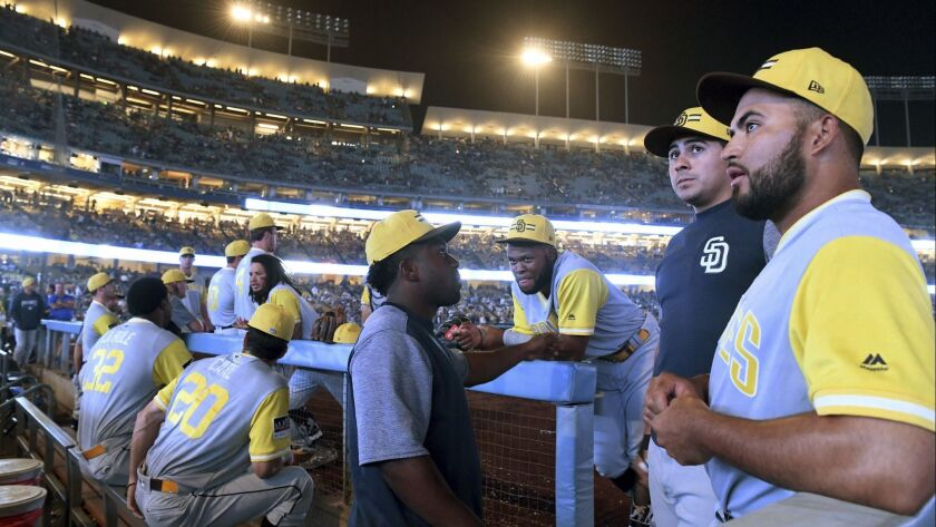 San Diego Padres wait in the dugout after the main stadium lighting went out during the 12th inning