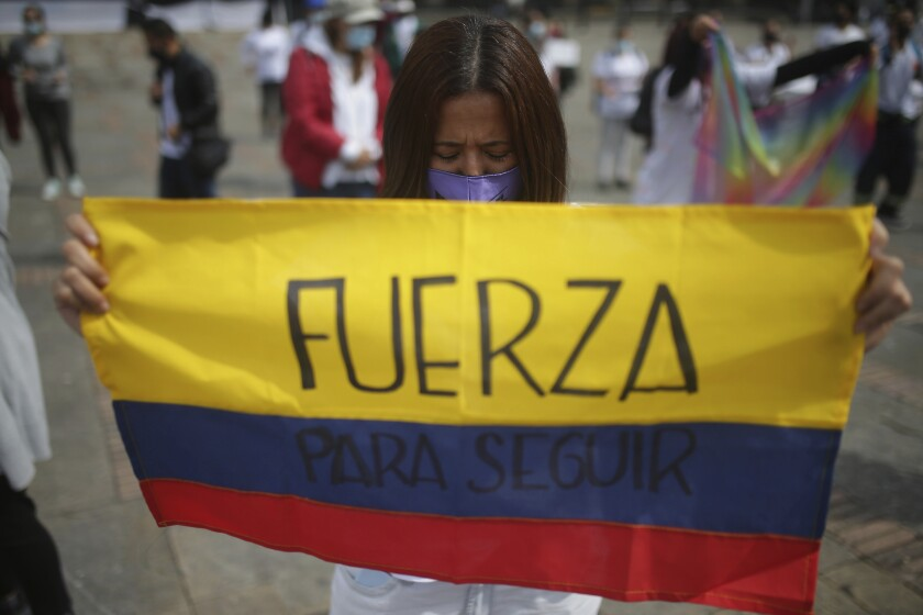 Woman holding Colombian flag and praying