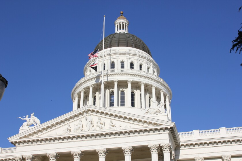 Flags fly at half-staff in front of the white dome of the California state Capitol building on a sunny day