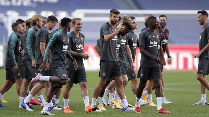 Barcelona's Gerard Pique, center, gestures during a training session at the Luz stadium.