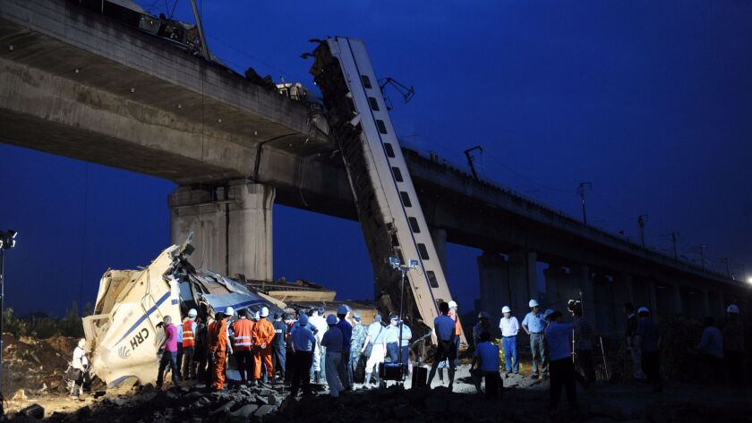 This photo taken on July 24, 2011 shows workers clearing wreckage after a Chinese high-speed train derailed and carriages fell off the elevated track.