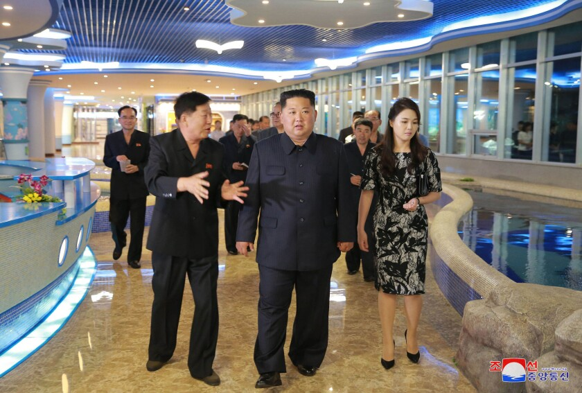 In an undated photo provided Saturday by the North Korean government, North Korean leader Kim Jong Un, center, and his wife, Ri Sol Ju, inspect a newly opened seafood restaurant in Pyongyang.